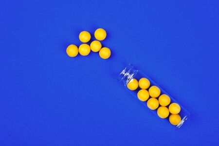 Minimalism style template for medical blog. Small glass bottle fwith small yellow pills spilled out blue background. Pharmaceutical concept. Medicine pills. Flat lay 写真素材