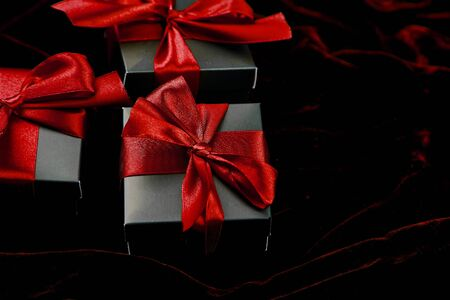 Luxury black gift boxes with red ribbon on shine velvet background. Christmas, birthday party presents. Father Day. Flat lay. Copy space. Top view. 写真素材