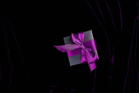 One luxury black gift boxe with violet ribbon on shine velvet background. Christmas, birthday party presents. Father Day. Flat lay. Copy space. Top view. 写真素材