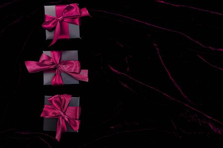 Luxury black gift boxes with pink ribbon on shine velvet background. Christmas, birthday party presents. Flat lay. Copy space. Top view.