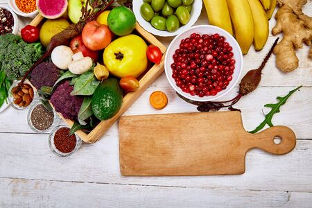 Selection of superfoods around cutting board on white background.