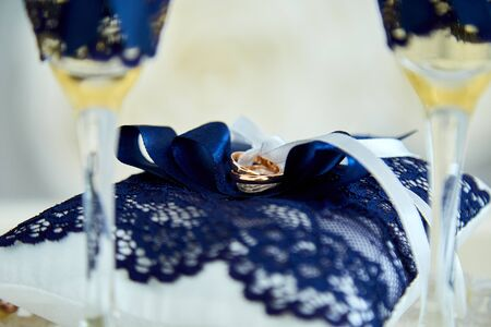 Two glasses of a champagne and pillow with wedding rings.