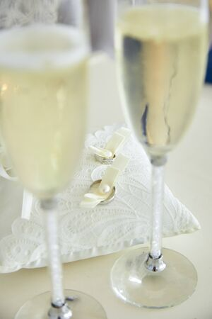 Two glasses of a champagne and pillow with wedding rings.  写真素材