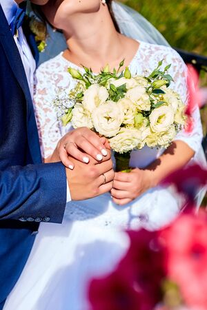 Wedding bouquet. The girl in a white dress and a guy in a suit sitting are holding a beautiful bouquet flowers and greenery. Unrecognizable 写真素材