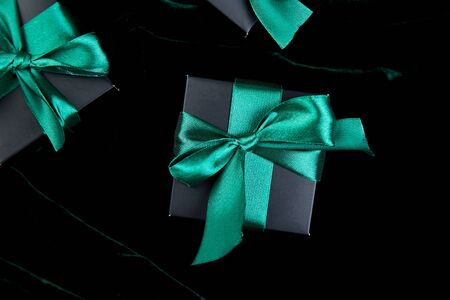 Luxury black gift boxes with green ribbon on shine velvet background. Flat lay. Copy space. Top view.