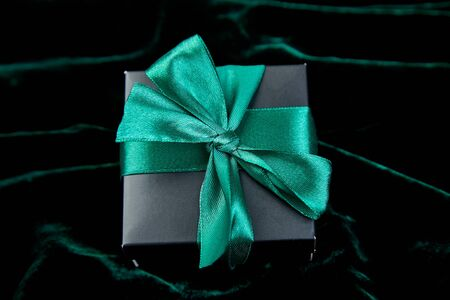 One luxury black gift boxe with green ribbon on shine velvet background. Flat lay. Copy space. Top view.