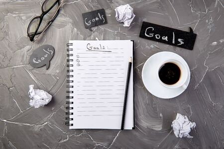Goals as memo on notebook with idea, crumpled paper, cup of coffee over on grey background. Top view. 写真素材