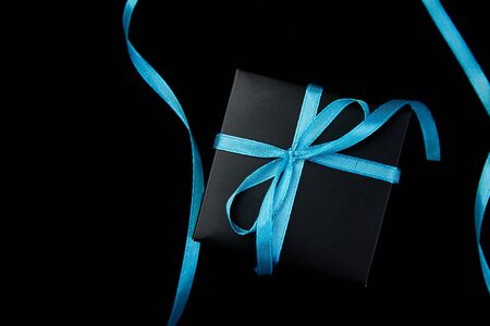 One luxury black gift boxes with blue ribbon on shine black background. Flat lay. Copy space. Top view.