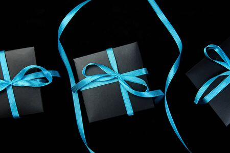Luxury black gift boxes with blue ribbon on shine black background. Flat lay. Copy space. Top view.