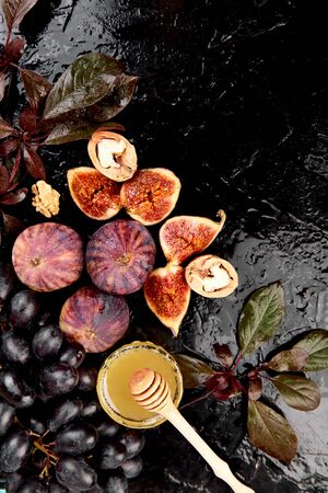 Autumn frame background. Autumn food still life with season fruits grape and figs, honey on a black table. Thanksgiving day. 写真素材