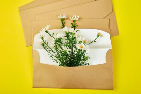 Gold envelope with a spring flower arrangement on yellow background. Flat lay, top view. Opened envelope. Festive greeting concept 写真素材