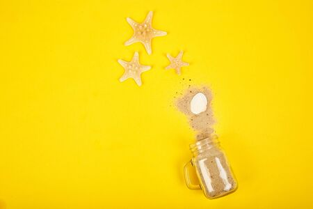 Starfishes and seashells, glass with sand on yellow background top view. Color concept of travel or vacation holidays.  Flat lay style. Banner