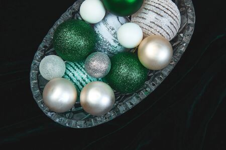 Christmas or New Year preparations. Flat lay of green, white and silver Christmas tree decoration toys, balls, in glass box on dark background, top view. Festive holiday mood