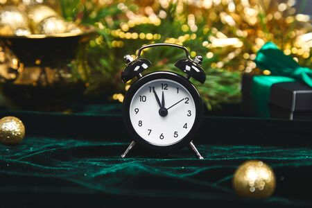 Christmas gift box, alarm clock and fir tree branch on table. Top view with copy space New Year is coming. Black clock and gold christmas decorations green velours glitte, shine background. Eve Time Concept