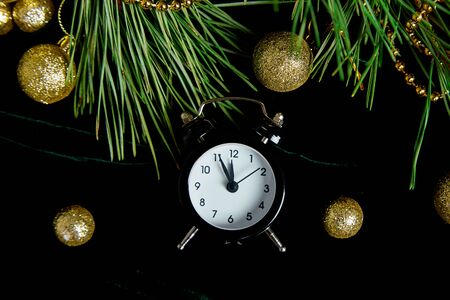 Black Alarm clock and fir tree branch, gold christmas decorations green velours glitte, shine background. Eve Time Concept on table. New Year is coming. Flat lay, top view. Christmas gift card. Banco de Imagens