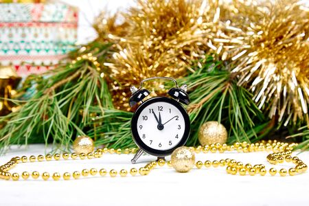 Eve Time Concept on table. New Year is coming. Black Alarm clock and fir tree branch, gold christmas decorations on white wooden background. Christmas gift card. Stock fotó