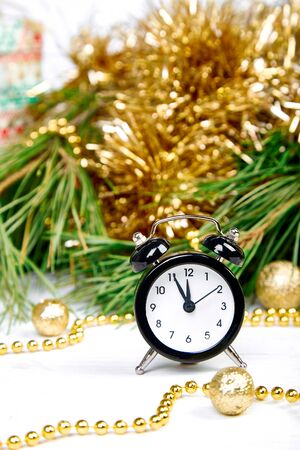Eve Time Concept on table. New Year is coming. Black Alarm clock and fir tree branch, gold christmas decorations on white wooden background. Christmas gift card. Banco de Imagens