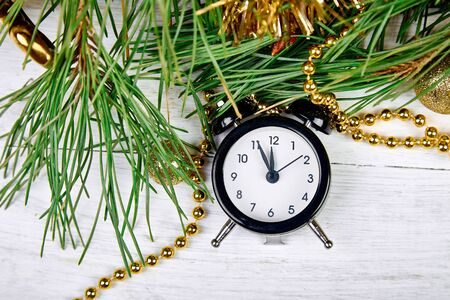 Black Alarm clock and fir tree branch, gold christmas decorations on white wooden background. Eve Time Concept on table. New Year is coming. Flat lay, top view. Christmas gift card. Copy space. Banco de Imagens