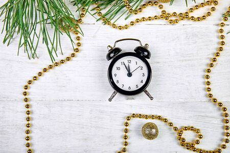 Black Alarm clock and fir tree branch, gold christmas decorations on white wooden background. Eve Time Concept on table. New Year is coming. Flat lay, top view. Christmas gift card. Copy space. Stock fotó