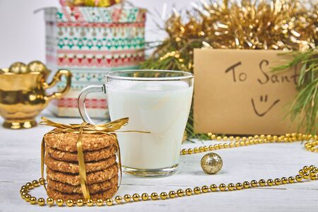 Christmas glass with milk and cookies For Santa on the table with Christmas Tree, gifts, decorations on white wooden background. Letter for Santa.