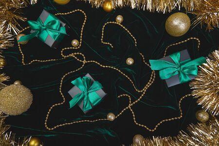 Christmas festive black gift boxes with green ribbon on velours glitte Stock fotó