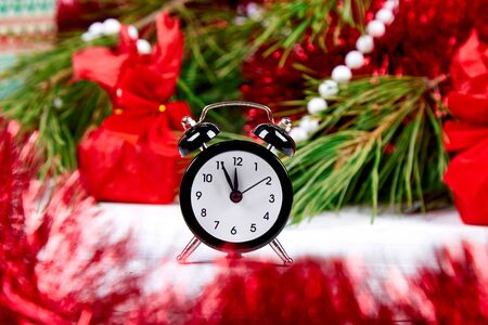 Black Alarm clock and fir tree branch, red christmas decorations on white wooden background. Eve Time Concept on table. New Year is coming. Christmas gift card.