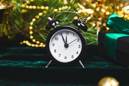 Christmas gift box, alarm clock and fir tree branch on table. Top view with copy space New Year is coming. Black clock and gold christmas decorations green velours, shine background. Eve Time Concept Stock fotó