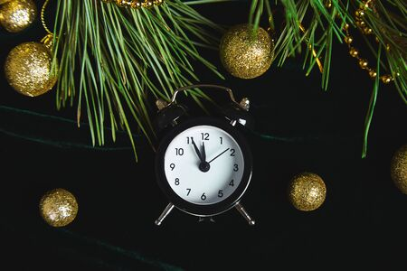 Black Alarm clock and fir tree branch, gold christmas decorations green velours glitte, shine background. Eve Time Concept on table. New Year is coming. Flat lay, top view. Christmas gift card. Stock fotó