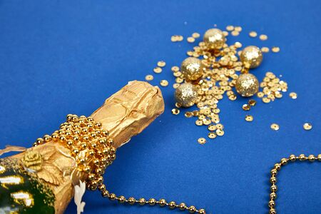 Gold champagne bottle with golden confetti on blue paper background. Birthday, wedding, christmas celebration festive concept. Top view. Flat lay. Copy space Stockfoto