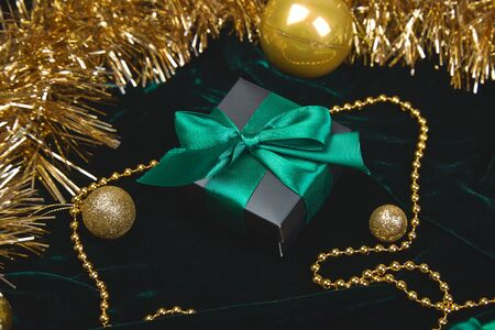 Christmas festive black gift boxes with green ribbon on velours glitte, shine gold  background. Copy space. Flat lay. Festive holiday mood. Stock fotó