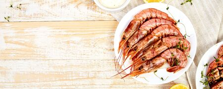 Banner with Grilled big tiger shrimps prawns on white plate with spices, lemon, fresh herbs on white wooden background, top view. Grilled seafood. Barbecue shrimps. Copy space. 写真素材 - 137801908