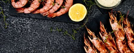 Banner with Grilled big tiger shrimps prawns on black slate plate with spices, lemon, fresh herbs on black background, top view. Grilled seafood. Barbecue shrimps. Copy space.