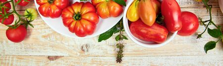 Banner with Mix of tomatoes background. Beautiful juicy organic red tomatoes on white wooden table background. Clean eating concept. Copy space, flat lay. Banco de Imagens