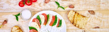 Banner with Italian caprese salad with sliced tomatoes, mozzarella cheese, basil, olive oil on wooden background. Top view with space for your text