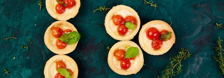 Banner with Mini tarts with cherry tomatoes with mozzarella cheese on green background. Top view. Copy space.
