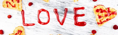 Banner with Belgian heart shaped waffle on white background. Word love made by jam