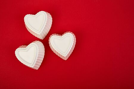 White ceramic hearts on red background. Flat lay composition. Romantic, St Valentines Day concept. Love. Copy space.