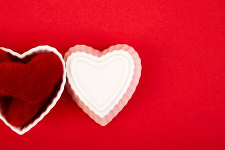 White ceramic hearts with red plush hearts on red background. Flat lay composition. Romantic, St Valentines Day concept. Love. Copy space.