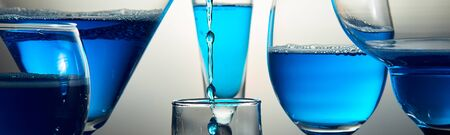 Banner of Many different glasses with blue champagne or alcohol drink cocktail, martini glasses. Pouring. Splash.
