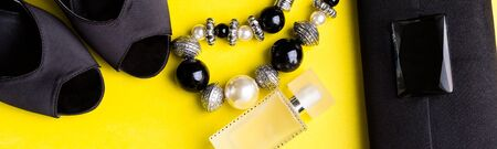 Banner of Fashion Lady Accessories Set. Black and yellow. Minimal. Black Shoes, bracelet, perfume and bag on yellow background. Flat lay