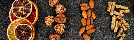 Banner of Healthy snacks - variety oat granola bar, rice crips, almond, kiwi, dried orange, on black background. Mix assortment. Top view. Diet food. Gluten free Vegan Banco de Imagens