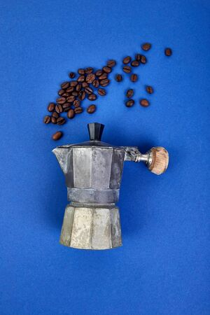 Flat lay of Coffee maker and beans blue trend background. Coffee love concept. Moka coffee pot. Espresso maker. Process of making natural coffee from beans. Top view. Copy space. 스톡 콘텐츠