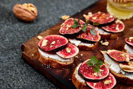 Bruschetta or ctostini with cottage cheese, figs and honey. Sandwich with figs and goat cheese.