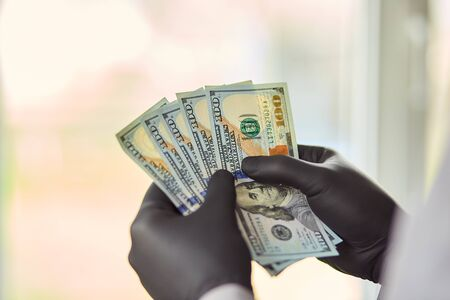 Man holding money dollars in hand in black medical gloves. Coronavirus crisis. Save money. Foto de archivo