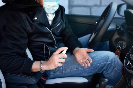 Man in protection mask sitting in the car, spraying hands antibacterial sanitizer spray for prevention coronavirus disease, health care concept.