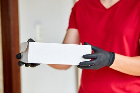 Delivery service under quarantine. Courier, delivery man in red in medical gloves safely delivers online purchases during coronavirus epidemic. Stay home, safe concept, contactless delivery.