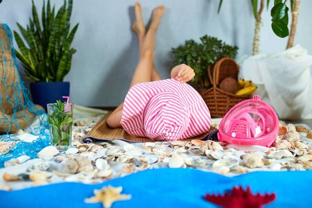 The girls in pink hat is lying on a fictional beach near the sea or ocean, sunbathes. Imitates summer sea beach vacation at home quarantine. Coronavirus home activity, funny, happy, crazy.