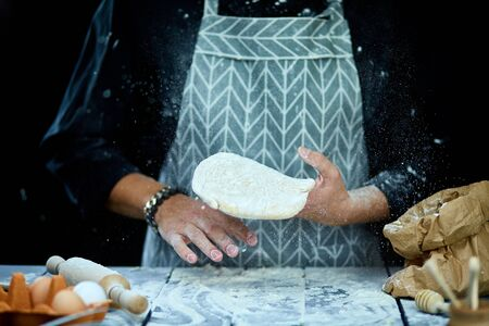 The man, chef cooks throws the dough, flying, freezing in motion. Cooking at home. White flour flying into air, Hands preparing dough