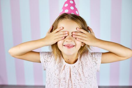 Little beautiful girl wearing birthday pink cap, waiting surprise, close her eyes, smiling with happy face. Happy birthday.