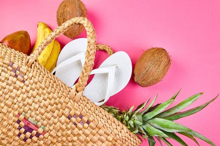 Flat lay of summer white flip flops wicker bamboo bag and fresh exotic fruits over pink background, top view, copy space. Summer beach vacation concept. Copy space.